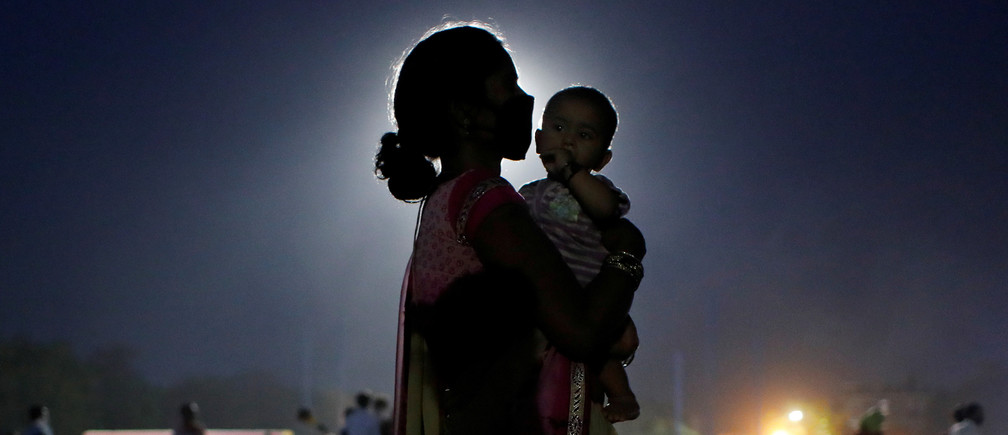 A woman and her baby wait for a bus to take them to a railway station to board a train to their home state of Uttar Pradesh, after a limited reopening of India's giant rail network following a nearly seven-week lockdown to slow the spreading of the coronavirus disease (COVID-19), in Ghaziabad in the outskirts of New Delhi, India, May 18, 2020.