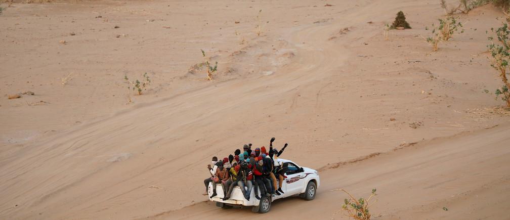 Los migrantes que cruzan el desierto del Sahara hacia Libia viajan en la parte trasera de una camioneta en las afueras de Agadez, Níger, el 9 de mayo de 2016.