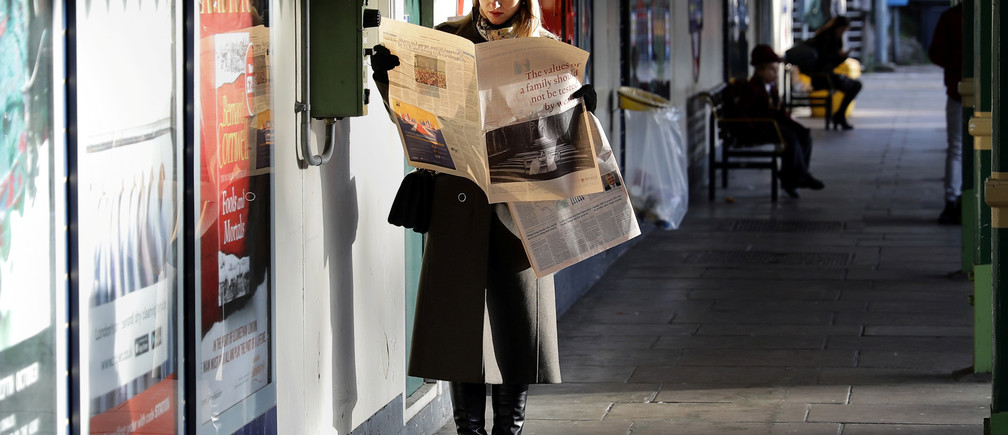 A woman reads a newspaper whilst waiting for a tube train on an autumn morning in London, Britain, October 30, 2017.      REUTERS/Kevin Coombs - RC14C0007EA0