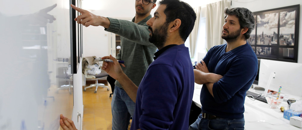 Employees of the D-ID startup company debate while looking at a whiteboard at the company's office in Tel Aviv, Israel February 7, 2018. Picture taken February 7, 2018. REUTERS/Amir Cohen - RC1D1124E700