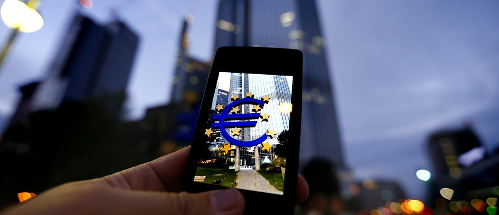 A passerby uses his smartphone to take a picture of the euro sign landmark in front of the headquarters of the European Central Bank (ECB) in Frankfurt September 2, 2013. The ECB council will hold its monthly meeting on Thursday, September 5. REUTERS/Kai Pfaffenbach (GERMANY - Tags: BUSINESS) - GM1E9930BUE01