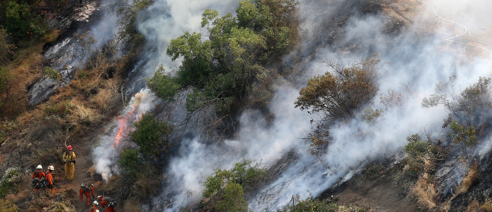 Firefighters halt the progress of a wildfire burning behind the Getty Center in Mandeville Canyon in Los Angeles, California, U.S., May 28, 2017. REUTERS/Lucy Nicholson - RTX380TG