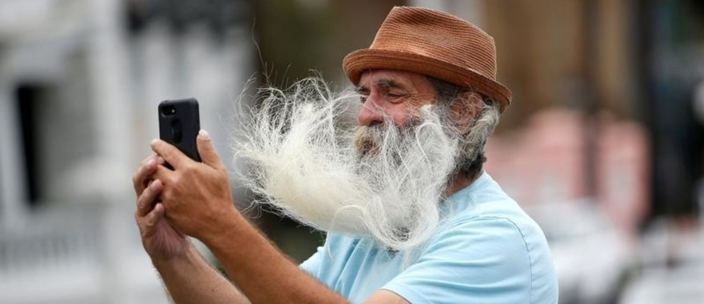 A man's facial hair blows in the wind as he takes a selfie along the waterfront ahead of the arrival of Hurricane Dorian in Charleston, South Carolina, U.S., September 4, 2019.  REUTERS/Randall Hill     TPX IMAGES OF THE DAY - RC1F11D4D700