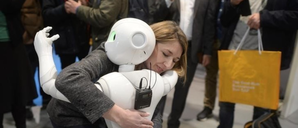 A woman embraces humanoid robot Pepper at the world's biggest computer and software fair CeBit in Hanover, Germany, March 14, 2015.