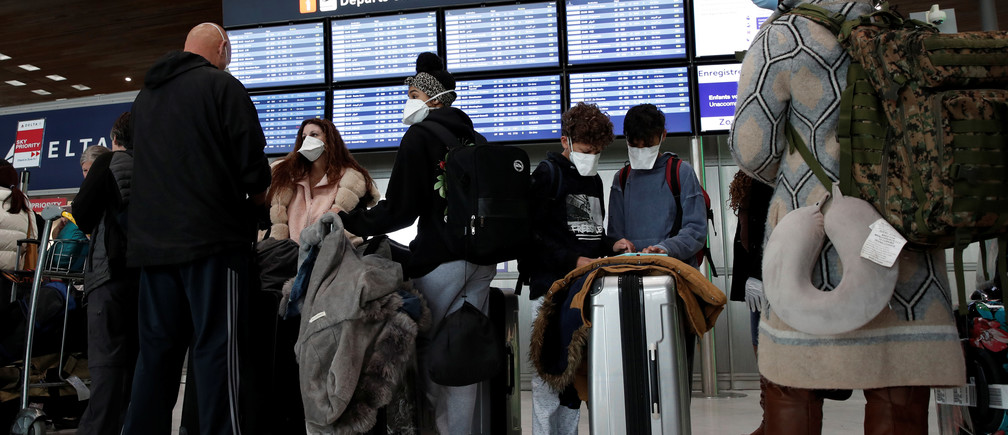 Travellers wearing protective face masks line up at the Delta Air Lines ticketing desk inside Terminal 2E at Paris Charles de Gaulle airport in Roissy, after the U.S. banned travel from Europe, as France grapples with an outbreak of coronavirus disease (COVID-19), March 12, 2020.