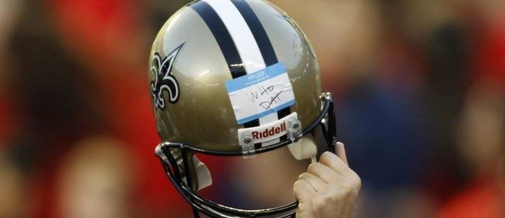 A member of the New Orleans Saints staff holds up a helmet during the NFL's Super Bowl XLIV football game against the Indianapolis Colts in Miami, Florida, February 7, 2010.  REUTERS/Carlos Barria (UNITED STATES) - LR1E628025PBF