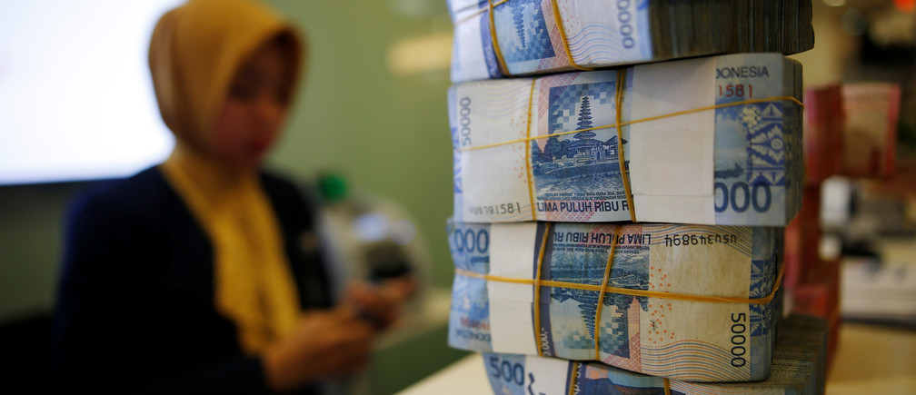 A bank teller counts rupiah banknotes at a branch inside Bank Mandiri headquarters in Jakarta, Indonesia December 10, 2015.