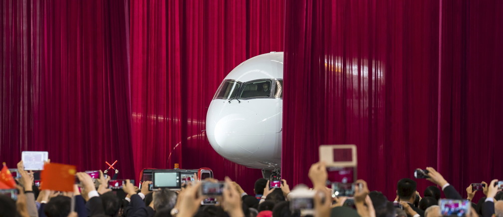 People take pictures and videos as the first C919 passenger jet made by the Commercial Aircraft Corp of China (Comac) is pulled out from behind a curtain during a news conference at the company's factory in Shanghai, November 2, 2015. Comac rolled out China's first homemade 158-seated C919 narrow body jet, which is meant to rival similar models from Airbus Group and Boeing Co. State television also showed footage of the aircraft rolling off the assembly line in Comac's Shanghai factory. In a statement, the company said it had already received 517 orders for the aircraft mainly from domestic firms. Picture taken November 2, 2015. REUTERS/China Daily CHINA OUT. NO COMMERCIAL OR EDITORIAL SALES IN CHINA. TPX IMAGES OF THE DAY.      - GF20000043741