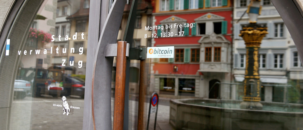 """A sticker reading """"Bitcoin accepted here"""" is displaye at the entrance of the Stadthaus town hall in Zug, Switzerland, August 30, 2016. Picture taken August 30, 2016.  REUTERS/Arnd Wiegmann  - RTX2OLUE"""
