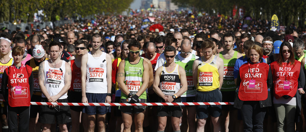 Runners observe a moment of silence before the start of the London Marathon in Greenwich, southeast London April 21, 2013. Undaunted by the Boston Marathon bombings, big crowds lined the route of the London Marathon on Sunday to cheer on some 36,000 runners who paid their respects to the Boston victims by wearing black ribbons and holding a 30-second silence before the start. ing off on the London Marathon on Sunday, under the watchful eyes of hundreds of extra police. REUTERS/Luke MacGregor  (BRITAIN - Tags: SPORT ATHLETICS) - LM1E94L0RTC01