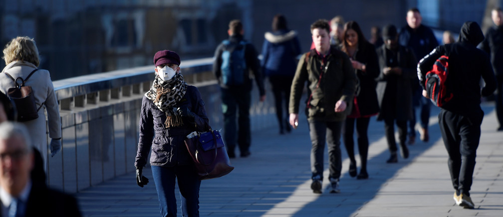 Commuters cross London Bridge with some wearing masks, as the spread of the coronavirus disease (COVID-19) continues, in London, Britain, March 23, 2020. REUTERS/Toby Melville - RC2MPF91KF6B