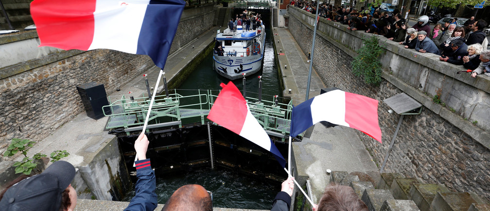 Supporters wave french flags as Jean-Luc Melenchon, candidate of the French far-left Parti de Gauche and candidate for the French 2017 presidential election  cruises on a barge on the canal de l'Ourcq in Paris, France, April 17, 2017.