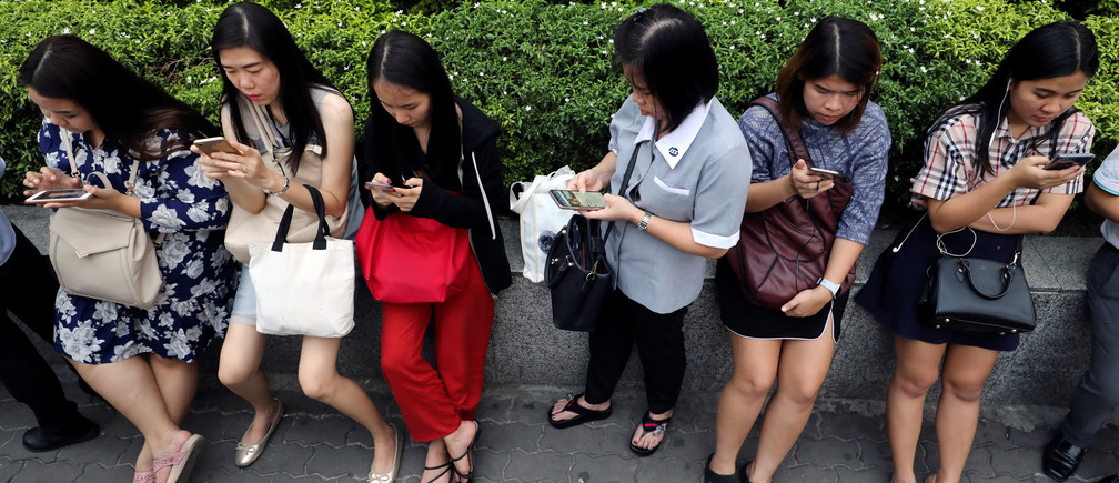 Women use their mobile phones while waiting for a bus at rush hour in Bangkok, Thailand October 4, 2018. REUTERS/Jorge Silva - RC150B3A10D0