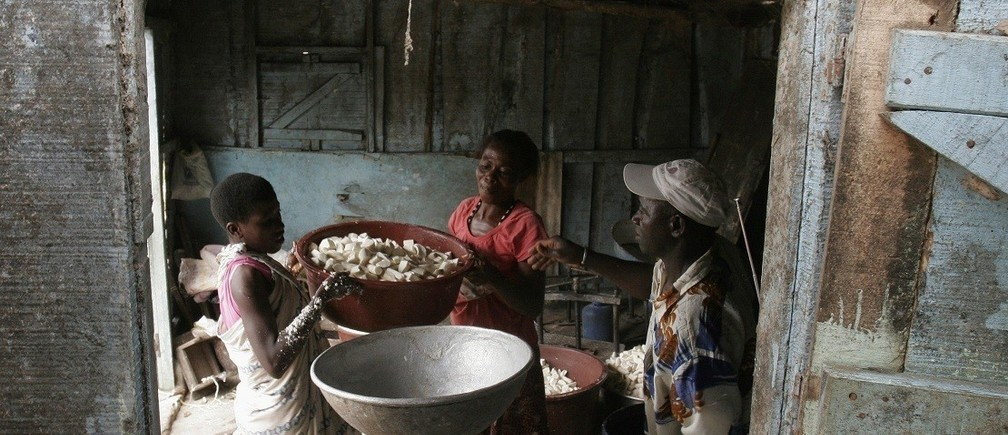 People prepare to grind cassava roots in Bingerville, near Abidjan, June 24, 2008. REUTERS/ Thierry Gouegnon (IVORY COAST) - RTX7A3V