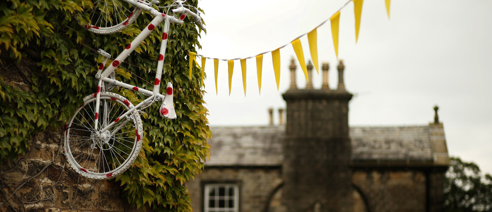 A bicycle decorated with polka dots hangs from the wall of a pub on the route of the Tour de France in Addingham, northern England June 17, 2014. Tour de France fever has hit the Yorkshire Dales, with yellow bicycles appearing in hedgerows, outside pubs and in people's front gardens. The county will host the start of this year's Tour de France and as the excitement builds, bicycle-themed decorations adorn the countryside.   Picture taken June 17, 2014.   REUTERS/Phil Noble   (BRITAIN - Tags: SPORT SOCCER SOCIETY)