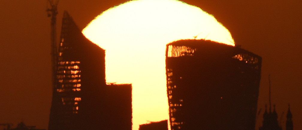 The sun is seen rising over skyscrapers in the City of London financial district in London, Britain, May 3, 2018.