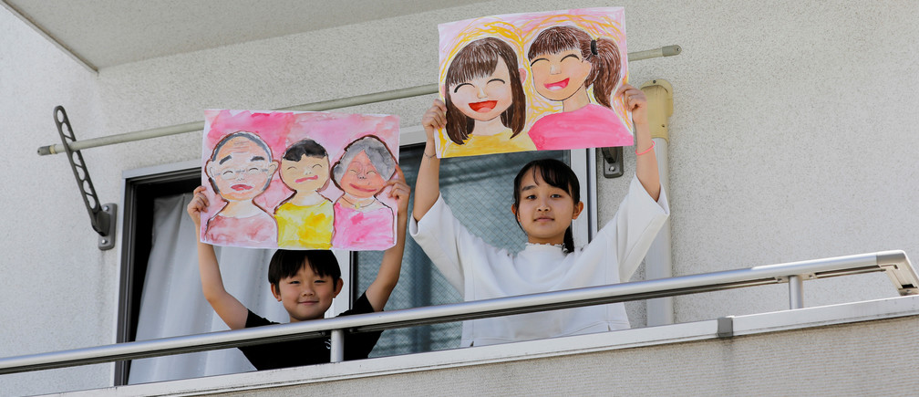 "Reku Matsui, 8, and Yaya Matsui, 12, pose for a photograph while holding pictures that they drew during the coronavirus disease (COVID-19) outbreak, as they stand on the balcony of their home in Tokyo, Japan, April 19, 2020. ""I miss being with my grandmother and my grandfather. Also, I want to go to my grandmother's house,"" said Reku, who drew a picture of himself standing in between his two smiling grandparents. Yaya, who drew a picture of herself and a friend said ""what I want to do the most right now is hang out with my friends."" REUTERS/Kim Kyung-Hoon     SEARCH ""CORONAVIRUS DRAWING"" FOR THIS STORY. SEARCH ""WIDER IMAGE"" FOR ALL STORIES. TPX IMAGES OF THE DAY - RC2BAG9KZSI9"