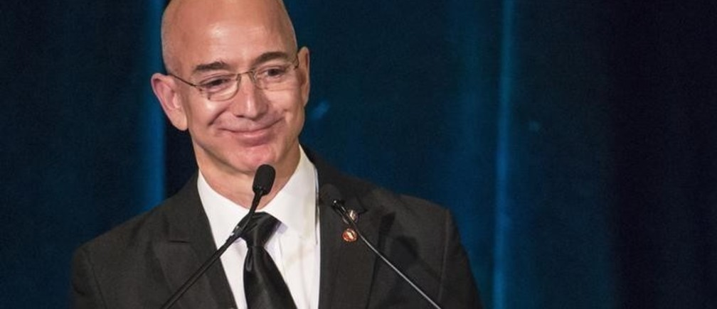 Amazon CEO and Chairman Jeff Bezos receives the Citation of Merit on behalf of the Apollo F-1 Search and Recovery Team at the 110th Explorers Club Annual Dinner at the Waldorf Astoria in New York March 15, 2014. The club, which promotes the scientific exploration of land, sea, air and space featured catering by chef and exotic creator Gene Rurka. Chef Rurka prepared a variety of dishes featuring an array of insects, wildlife, animal body parts and invasive species. REUTERS/Andrew Kelly (UNITED STATES - Tags: SOCIETY BUSINESS SCIENCE TECHNOLOGY FOOD)