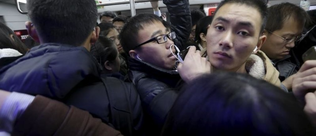 An Zi, is squashed amongst other commuters in a subway train on his way to work in Beijing, China