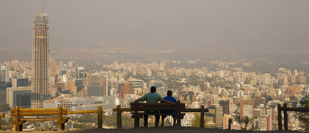 A man (L) sits with his son while enjoying the view of the Andes Mountains Range at the San Cristobal Hill in Santiago de Chile February 8, 2012.
