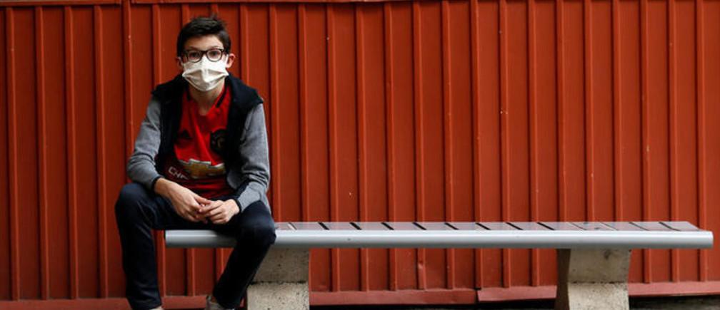 Un estudiante que regresa a la escuela en Niza, Francia, usando una máscara facial protectora.