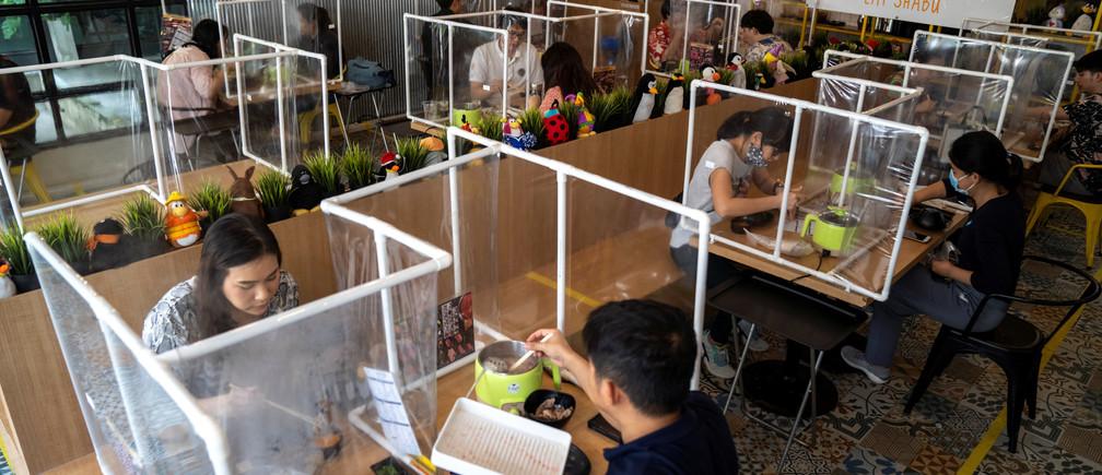 La gente almuerza en el restaurante de ollas calientes Penguin Eat Shabu que reabrió después de la flexibilización de las restricciones con la aplicación de una barrera de plástico y medidas de distanciamiento social para prevenir la propagación de la enfermedad coronavirus (COVID-19) en Bangkok, Tailandia, el 8 de mayo de 2020.