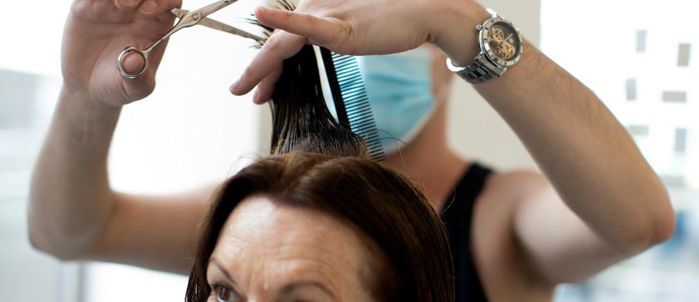 Manuel, peluquero de la peluquería Hair Concept Grecht, usa una máscara protectora mientras trabaja durante el brote de la enfermedad coronavirus global (COVID-19) en Viena, Austria, el 2 de mayo de 2020.
