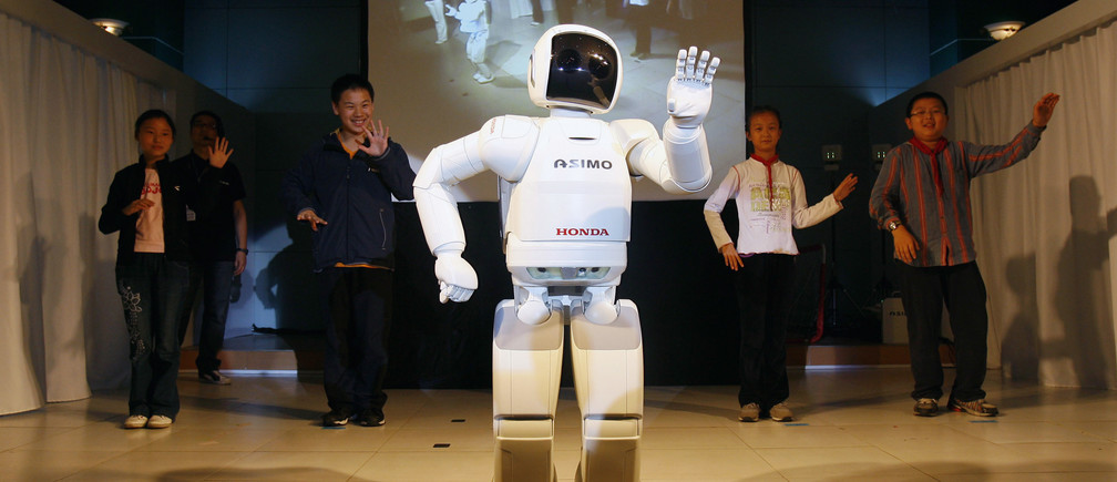 "Honda's humanoid robot ""Asimo"" leads pupils to dance at a primary school during its first appearance in Wuhan, Hubei province May 26, 2009. Picture taken May 26, 2009. REUTERS/Stringer (CHINA SCI TECH) CHINA OUT. NO COMMERCIAL OR EDITORIAL SALES IN CHINA - GM1E55R12GL01"
