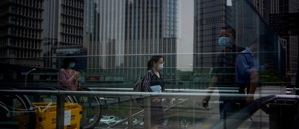 People wearing protective face masks walk past office buildings in Lujiazui financial district in Pudong, in Shanghai, following the coronavirus disease (COVID-19) outbreak, China June 4, 2020. REUTERS/Aly Song     TPX IMAGES OF THE DAY - RC2E2H969UFX