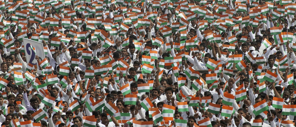 Employees of Sahara Group wave miniature national flags before singing India's national anthem in the northern Indian city of Lucknow May 6, 2013. More than 100,000 employees of the company attempted to create a new world record by singing the country's national anthem together at the same place in identical uniforms, said organisers.   REUTERS/Pawan Kumar (INDIA - Tags: BUSINESS SOCIETY) - GM1E9561PKB01