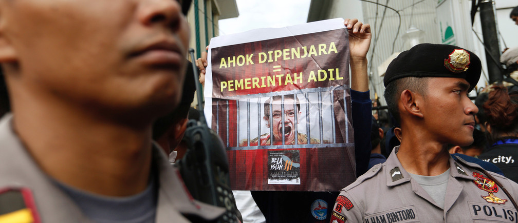 "A protester holds a banner outside a court during the first day of the blasphamy trial of Jakarta's Governor Basuki Tjahaja Purnama, also known as Ahok, in Jakarta, Indonesia December 13, 2016. The banner reads, ""Ahok in prison = A fair government"". REUTERS/Darren Whiteside - RTX2UQS2"
