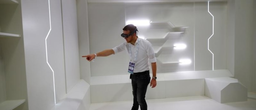 A gamer points to a virtual item in an empty room as he wears augmented reality goggles during the media day of Europe's leading digital games fair Gamescom, which showcases the latest trends of the computer gaming scene, in Cologne, Germany, August 20, 2019. REUTERS/Wolfgang Rattay - RC12C51EB1C0