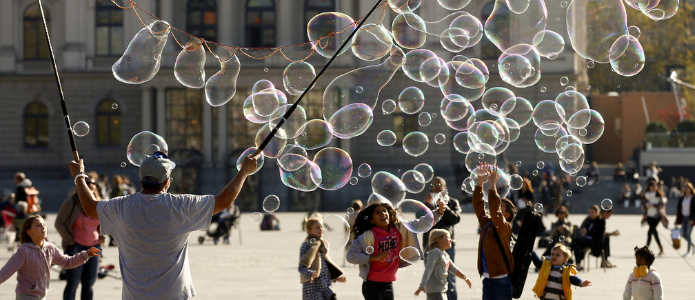 Gunnar Jauch blows big soap bubbles during sunny autumn weather at a square in front of the opera house in Zurich October 29, 2014.  REUTERS/Arnd Wiegmann