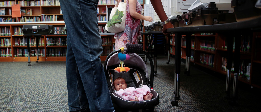 Kaia Kersaint, 10 weeks, waits patiently as her father Tino Kersaint and mother Koali Kersaint cast their votes for Georgia's 6th Congressional District special election at Livsey Elementary School in Tucker, Georgia, U.S., June 20, 2017.  REUTERS/Chris Aluka Berry - RTS17WQW