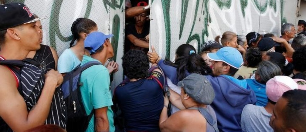 People push a door while they gather to try to buy pasta outside a supermarket in Caracas, Venezuela, June 10, 2016
