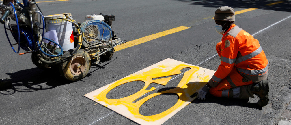 A worker paints a sign representing a cyclist on a new cycling path in Vincennes near Paris prior to the gradual lifting of lockdown restrictions during the outbreak of the coronavirus disease (COVID-19) in France, May 8, 2020. REUTERS/Charles Platiau - RC2DKG9GV0D8
