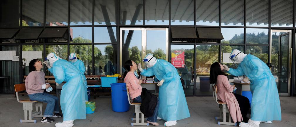 Trabajadores médicos de un hospital recogen hisopos de profesores de secundaria para realizar pruebas de ácido nucleico en una escuela, tras el brote de la enfermedad coronavirus (COVID-19), en Yichang, provincia de Hubei, China, el 27 de abril de 2020.