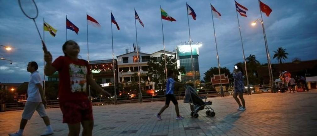 People walk past Asean countries's flags near Mekong river, ahead of the ASEAN Summit in Vientiane, Laos September 5, 2016. REUTERS/Soe Zeya Tun  - D1AETZOEXIAB