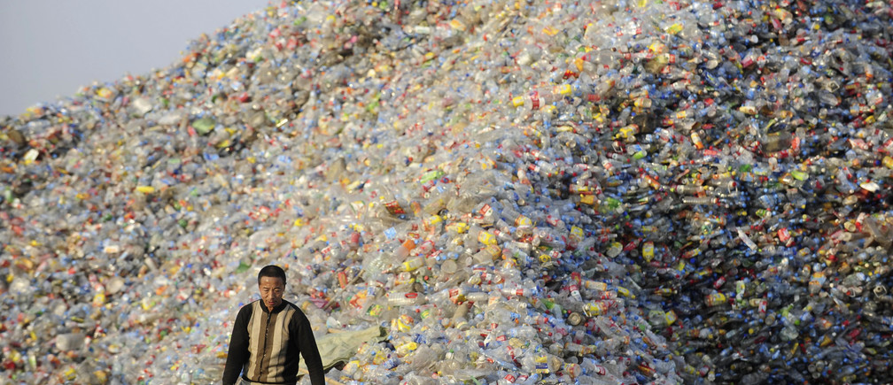A labourer stands next to a pile of plastic bottles at a recycling centre in Wuhan, Hubei province December 21, 2010. Picture taken December 21, 2010. REUTERS/China Daily (CHINA - Tags: ENVIRONMENT IMAGES OF THE DAY) CHINA OUT. NO COMMERCIAL OR EDITORIAL SALES IN CHINA - GM1E6CM0YLW01