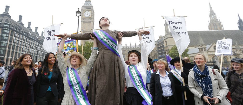 Performers dressed in period costume re-enact a march on Parliament by the suffragettes during a rally by feminist organisations to demand equality for women, in Westminster, central London, October 24, 2012. Women who earned less than men on the same pay grade when they worked for a local authority today won a battle for equal pay compensation at the UK's highest court according to local media reports.  REUTERS/Andrew Winning (BRITAIN - Tags: POLITICS SOCIETY) - LM1E8AO11ZP01