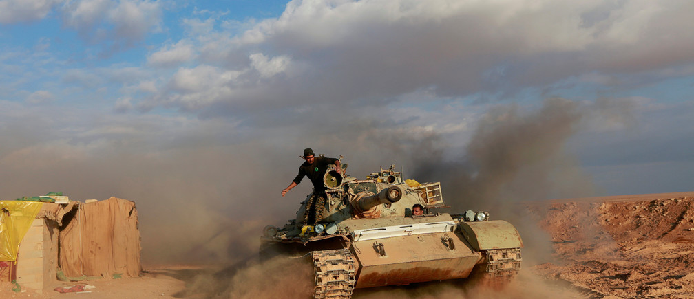 Popular Mobilisation Forces (PMF) fighters ride in a tank near the Iraqi-Syrian border in al-Qaim, Iraq.