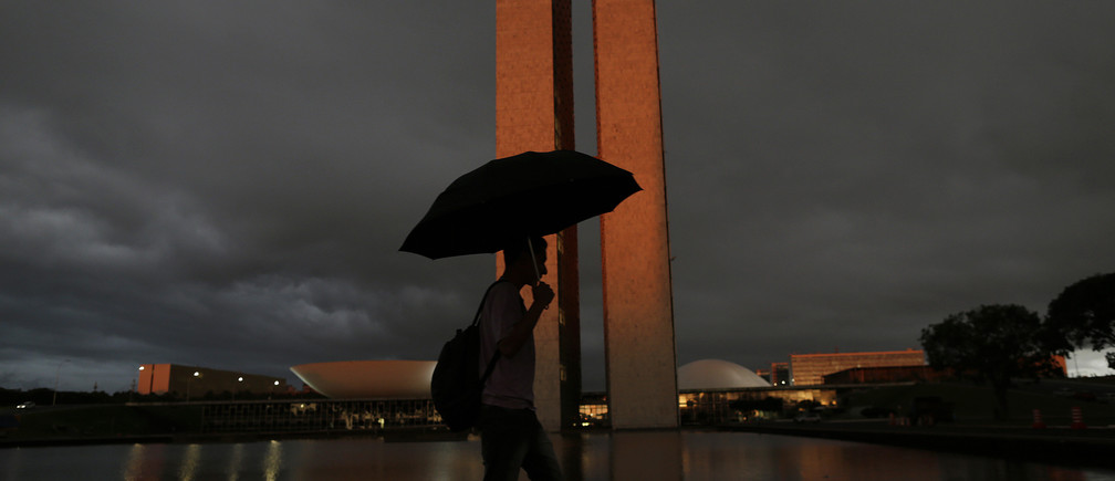 A man with an umbrella walks past Brazil's National Congress headquarters in Brasilia January 22, 2015.