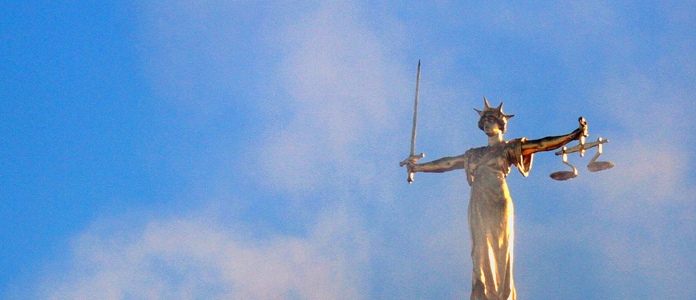 A statue of the figure of 'Justice' is seen above the Old Bailey court in London November 18, 2005. Three man charged with terrorism offences, including conspiracy to murder and conspiracy to cause explosion, will appear under tight security at the Old Bailey on Friday. ECONM UNICS REUTERS/Kieran Doherty - RP2DSFHMEKAB