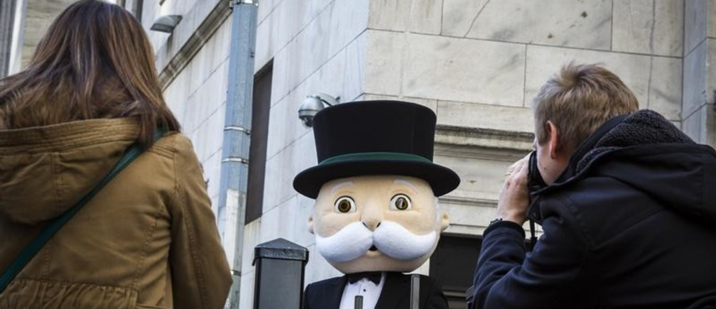 """A person dressed as the character """"Rich Uncle Pennybags"""" from Monopoly poses during a photo shoot outside the New York Stock Exchange in New York March 12, 2015. REUTERS/Lucas Jackson (UNITED STATES - Tags: SOCIETY) - GM1EB3D0AS001"""