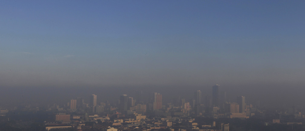Smog from the New Year revelry covers high rise buildings in Manila January 1, 2014.  REUTERS/Romeo Ranoco (PHILIPPINES - Tags: SOCIETY CITYSCAPE ENVIRONMENT) - GM1EA11127R01
