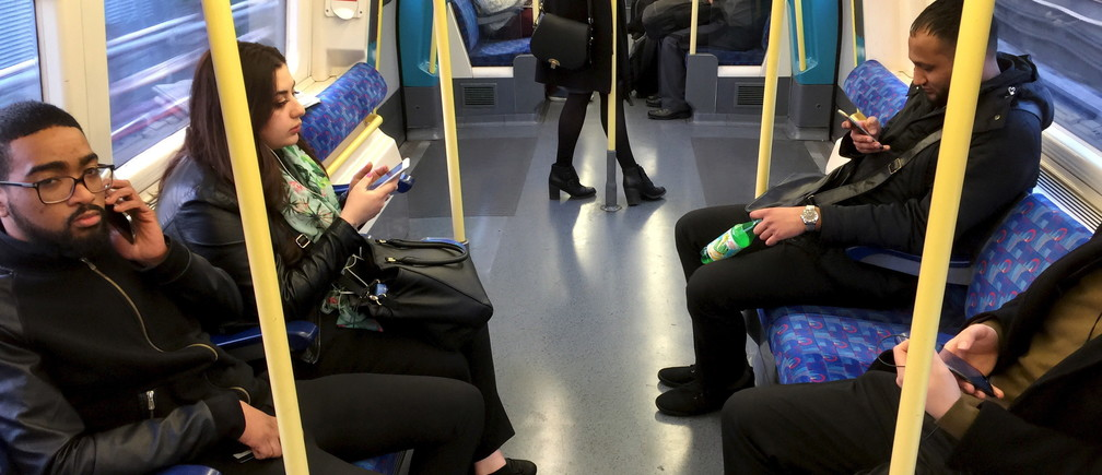 Commuters use their mobile devices on an underground tube train in London April 8, 2015.