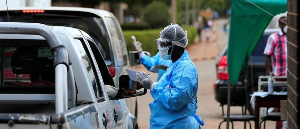 A health worker screens and sanitises visitors to prevent the spread of coronavirus disease (COVID-19) outside a hospital in Harare, Zimbabwe March 26, 2020. REUTERS/Philimon Bulawayo - RC2ORF9BW9VP