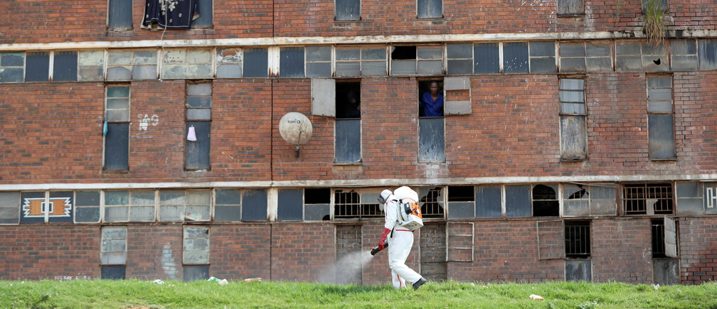 Residents look out of the window as a worker wearing protective gear sprays disinfectant to sanitise parts of the Alexandra's Madala Men's Hostel during a 21-day nationwide lockdown to try to contain the coronavirus disease (COVID-19) outbreak, in Alexandra, South Africa April 1, 2020. REUTERS/Siphiwe Sibeko     TPX IMAGES OF THE DAY - RC2QVF94DL78