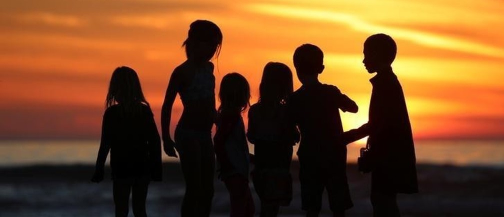 Children watch the sun set as they inspect tide pools during low tide in Solana Beach, California, U.S., January 4, 2018.      REUTERS/Mike Blake