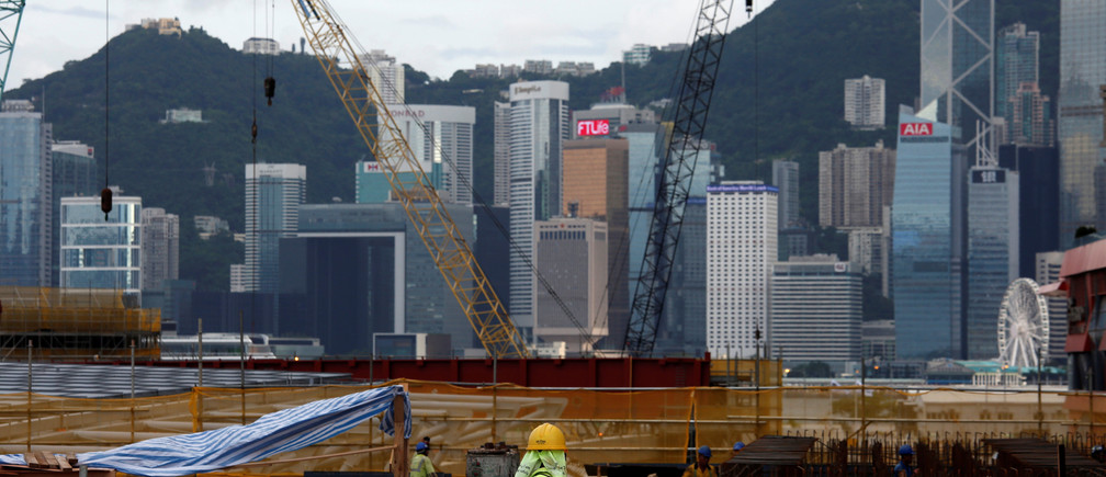 A worker stands on a construction site as part of the West Kowloon Terminus project for the Guangzhou-Shenzhen-Hong Kong Express Rail Link in Hong Kong, China July 21, 2017. Picture taken July 21, 2017. REUTERS/Bobby Yip - RTX3CSAC